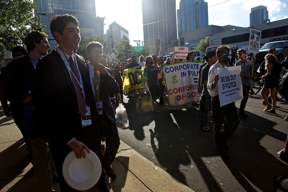 Convention attendees watch as Occupy DNC demonstrators walk through the streets during the 2012 Democratic National Convention on Wednesday, September 5, 2012 in Charlotte, NC.