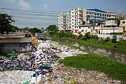 Environmental pollution on the river banks surrounding some of the textile industry buildings of Savar Upazila, a district of Dhaka, Bangladesh.  30th September 2018. Here a community living next to the garment industries sort and grade through large piles of discarded textiles. The garment business is the main industry of Savar Upazila, a district in the northern part of Dhaka.  (photo by Andrew Aitchison / In pictures via Getty Images)