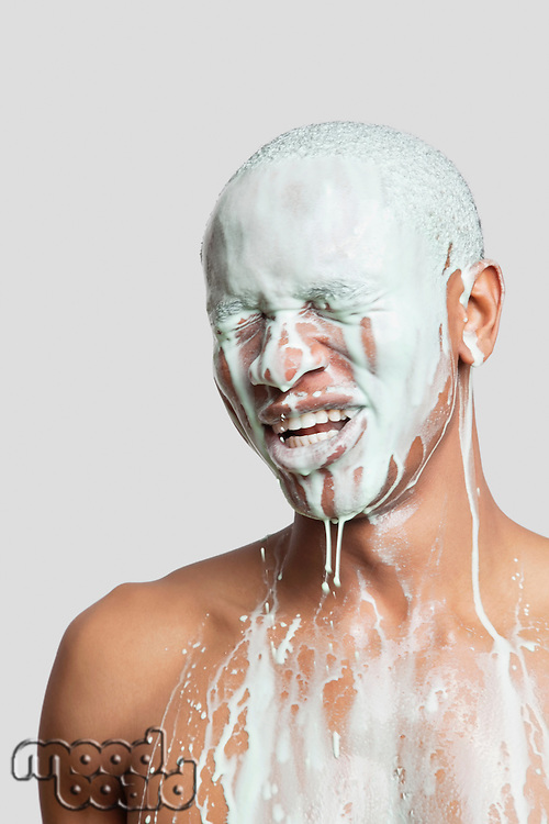 Shirtless young man with face covered in paint against gray background