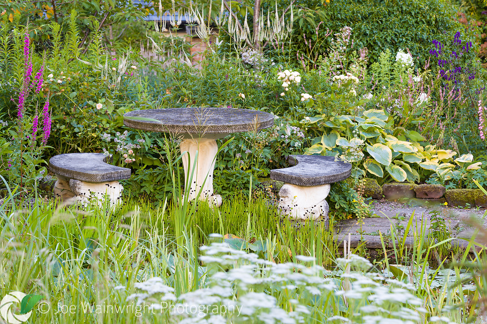 A pondside table and benches at Bluebell Cottage Gardens, Cheshire - photographed in July. Planting includes Lythrum, Hostas and Veronicastrums