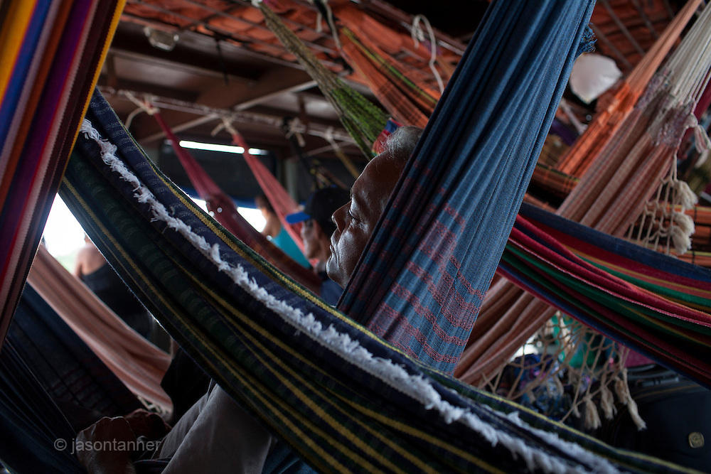 A man catch some sleep in his hammock aboard the Avenger. The Avenger III is a passenger ship making the twice a month journey from the frontier town of Tabatinga in the Tr&ecirc;s Fronteiras region of Northwestern Brazil, to the capital of the State of Amazonas, Manaus. It&rsquo;s also where the Rio Amazonas enters Brazil from its source in neighboring Peru. <br /> <br /> Carrying passengers and crew totaling almost 200 and small cargo, the ship meanders its way along the Rio Amazonas and Rio Solimoes for four days and three nights. Stopping at half a dozen or so makeshift ports en-route, the service provides a vial link for communities along the river to get products to the city and more importantly, in the absence of roads or airfields, provide a means for the sick to reach care in the city of Manaus.<br /> <br /> For those not fortunate to be accommodated in one of the two or three cabins available, home is space found for a self supplied hammock amongst the kaleidoscopic web of coloured fabrics. <br /> <br /> By the second day, negotiating a stroll from port to starboard can seem more like negotiating an assault course of tangled ropes and personal baggage deliberately piled high to protect ones personal space.<br /> <br /> Food served three times daily is adequate, a staple of soups, chicken, rice and noodles. An &lsquo;entertainment&rsquo; deck on the top floor provides ample opportunity to be social engaging in card and board games with beer swilling, chain smoking locals.