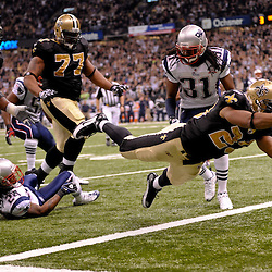 2009 November 30:  New Orleans Saints running back Pierre Thomas (23) dive past New England Patriots safety Brandon Meriweather (31) for a touchdown during the first half at the Louisiana Superdome in New Orleans, Louisiana.