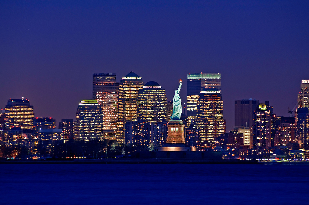 New York City Skyline and Statue of Liberty at dusk New York harbor