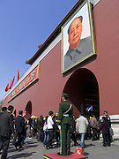 people entering the Forbidden City with Mao Zedong?s painted portrait hanging above the entrance gate