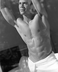 muscular man in a towel looking out a window