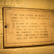 A sign on the wall detailing how to escape if bomb debris is blocking the door at the Churchill War Rooms in London. The museum, one of five branches of the Imerial War Museums, preserves the World War II underground command bunker used by British Prime Minister Winston Churchill. Its cramped quarters were constructed from a converting a storage basement in the Treasury Building in Whitehall, London. Being underground, and under an unusually sturdy building, the Cabinet War Rooms were afforded some protection from the bombs falling above during the Blitz.