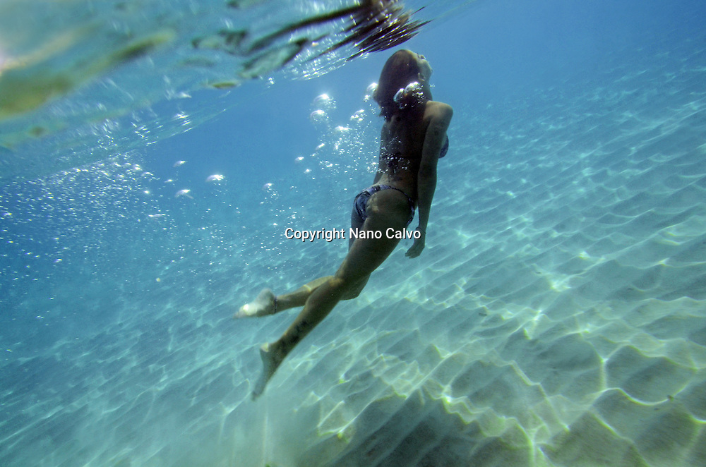 Young woman swims underwater in the beautiful waters of Menorca, Spain