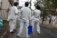 Workers gather outside their hotel, at 5.30am, to await the bus which will transfer them to the Fukushima Daiichi Nuclear Plant, where they will work in the clean up process of destruction caused by the March 11th earthquake and tsunami,  in Iwaki-Yumoto, Miyage prefecture, Japan, Friday 8th July 2011.