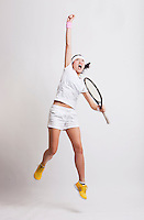 Young Asian female tennis player with racket jumping in excitement against white background