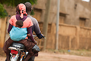 A woman and her child ride on the back of a motorcycle at the Badegna community health center in the town of Kita, Mali on Sunday August 29, 2010.