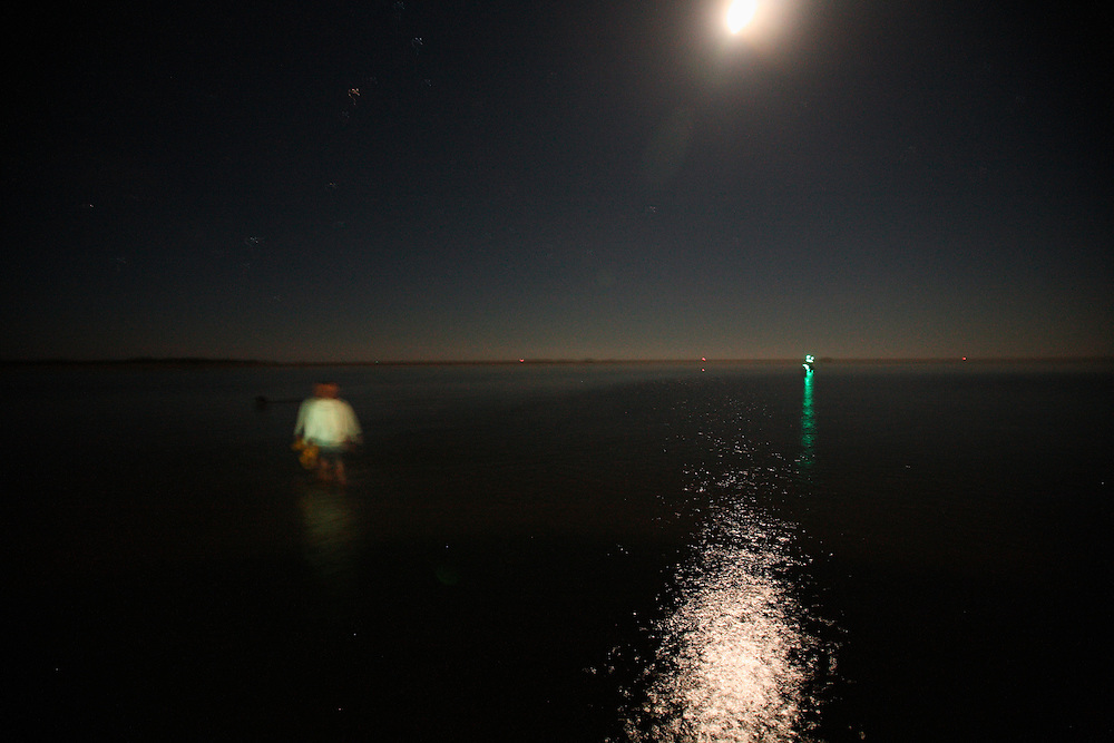 A walks on a shoal in Ocracoke Inlet at night. Located at the southernmost tip of North Carolina's Outer Banks, Ocracoke Inlet is part of the Cape Hatteras National Seashore and has fast currents, sandbars and shoals that make navigation extremely difficult.