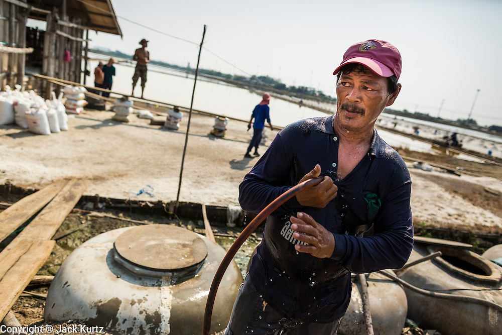 """28 MARCH 2014 - NA KHOK, SAMUT SAKHON, THAILAND: A Thai worker cools off with tap water on a salt farm in Samut Sakhon province. Thai salt farmers south of Bangkok are experiencing a better than usual year this year because of the drought gripping Thailand. Some salt farmers say they could get an extra month of salt collection out of their fields because it has rained so little through the current dry season. Salt is normally collected from late February through May. Fields are flooded with sea water and salt is collected as the water evaporates. Last year, the salt season was shortened by more than a month because of unseasonable rains. The Thai government has warned farmers and consumers that 2014 may be a record dry year because an expected """"El Nino"""" weather pattern will block rain in mainland Southeast Asia. Salt has traditionally been harvested in tidal basins along the coast southwest of Bangkok but industrial development in the area has reduced the amount of land available for commercial salt production and now salt is mainly harvested in a small parts of Samut Songkhram and Samut Sakhon provinces.    PHOTO BY JACK KURTZ"""