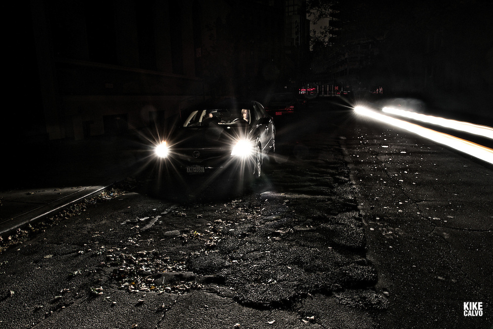 Driver waits in his car.  After Hurricane Sandy, in pitch dark downtown, New Yorkers experienced one of the darkest nights in history, including Halloween.
