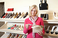 Mature woman looking at price tag of purse in store