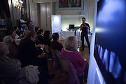 "Dave Walsh talking about his Arctic photographs, his time on Greenpeace ships, and his friends currently being held by Russian authorities in Murmansk. ""There's six billion people on this planet, we can't leave it up to 30 activists to be our consience"". Arctic Nocturne Event in Support of the Greenpeace 30 Activists at the Bibliotheque de Laeken, in Brussels, with speakers Neil Hamilton of Greenpeace, IPCC contributor Philippe Huybrechts and photographer Dave Walsh. Photograph by Ryan le Garrec."