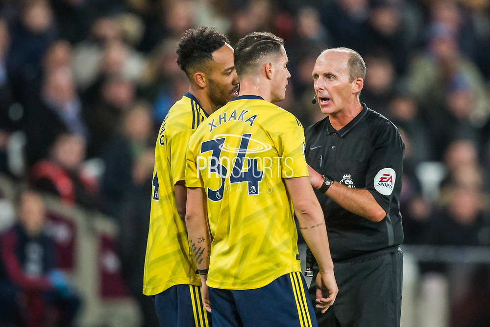 Mike Dean (Referee) talking with Granit Xhaka (Arsenal) & Pierre-Emerick Aubameyang (Capt) (Arsenal) during the Premier League match between West Ham United and Arsenal at the London Stadium, London, England on 9 December 2019.