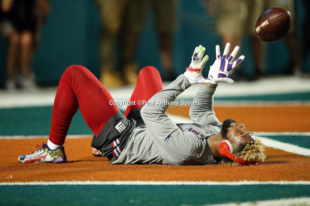 New York Giants wide receiver Odell Beckham Jr. (13) catches an over the head pass lying on the grass while warming up before the NFL week 14 regular season football game against the Miami Dolphins on Monday, Dec. 14, 2015 in Miami Gardens, Fla. The Giants won the game 31-24. (©Paul Anthony Spinelli)
