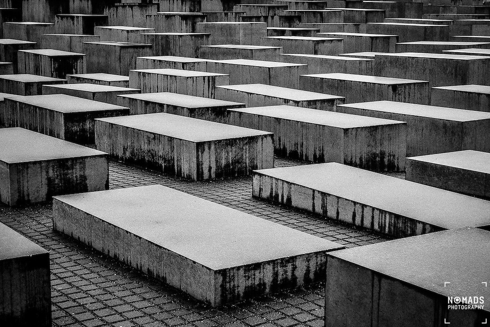"The Memorial to the Murdered Jews of Europe, also known as the Holocaust Memorial, is a memorial in Berlin to the Jewish victims of the Holocaust, designed by architect Peter Eisenman and engineer Buro Happold. It consists of a 19,000m2 site covered with 2,711 concrete slabs or ""stelae"", arranged in a grid pattern on a sloping field."