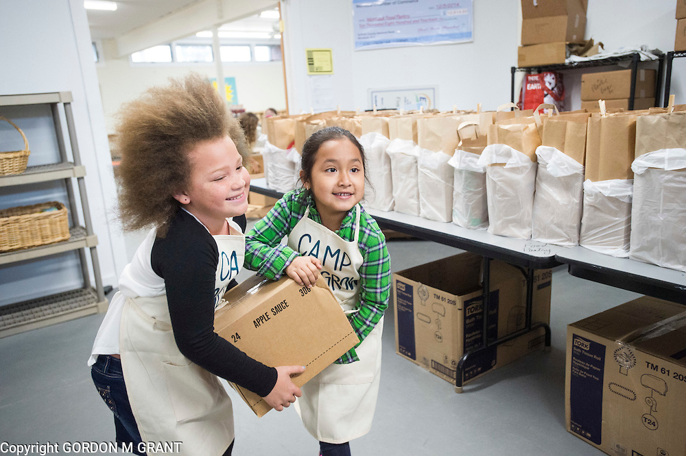 Kaia Wetzel, 7, left, and ??? ???, members of the non-profit Camp SoulGrow, help to stock food at the Montauk Food Pantry at St. Therese Church in Montauk, March 14, 2016.