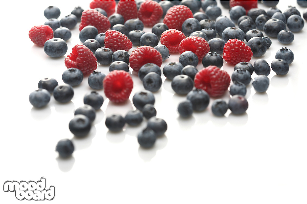 Raspberries and blueberries on white background