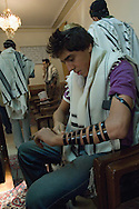 Tehran, Iran. October 22, 2007-.A teenager wraps his arm with Tefillin or Shel yad, getting ready for prayers. According to Jewish Law, they should be worn during weekday morning prayer services.