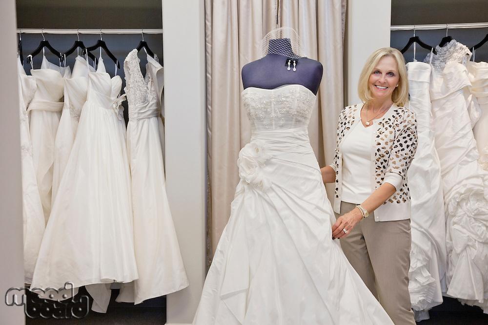 Portrait of a happy senior female adjusting wedding dress on mannequin in bridal store