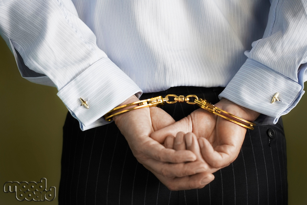 Businessman standing with hands handcuffed behind back mid section back view
