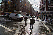 A man stands in the road talking on his phone waiting for a white van to pass so he can cross the road on Broome Street and Mott Street, Manhattan, New York City, New York, United States of America.  Snow is piled up on the side of the streets following a record breaking snow storm in January 2016.  (photo by Andrew Aitchison / In pictures via Getty Images)