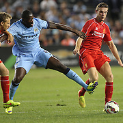 Yaya Touré, (centre), Manchester City, is challenged by Lucas Leiva, (left) and Jordan Henderson, Liverpool, during the Manchester City Vs Liverpool FC Guinness International Champions Cup match at Yankee Stadium, The Bronx, New York, USA. 30th July 2014. Photo Tim Clayton