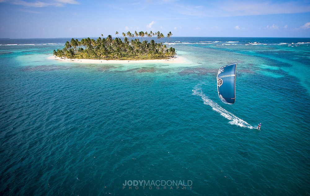 Kiteboarder glides across tranquil blue lagoon with lone palm covered island in the background in the San Blas, Panama