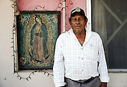 Resident of El Canal, Tamaulipas, Mexico has his portrait taken beside his shrine to the Virgin of Guadalupe