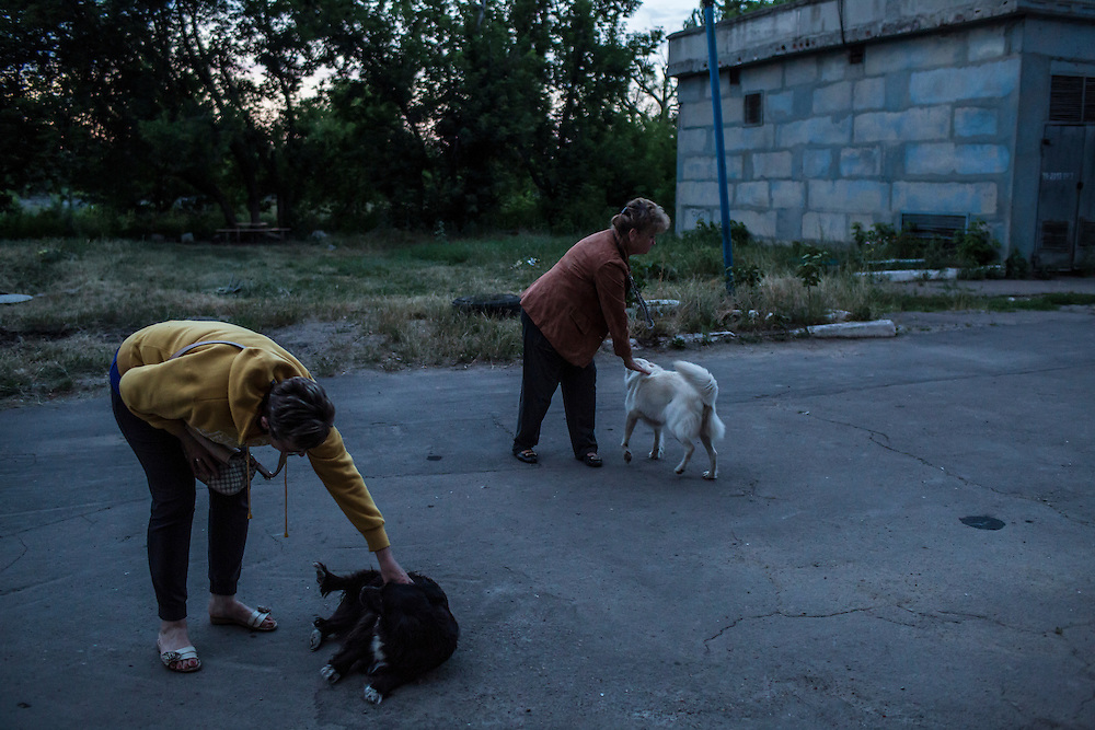 AVDIIVKA, UKRAINE - JULY 9, 2016: Women who live in an apartment building near the front lines, where a number of Ukrainian paratroopers are based, pet dogs outside their building in Avdiivka, Ukraine. The town is now one of the most active areas of fighting along the line of control between the Ukrainian government and Russian-backed rebels. CREDIT: Brendan Hoffman for The New York Times