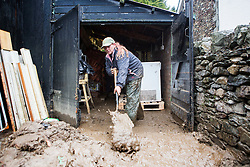 © Licensed to London News Pictures. 08/12/2015. Glen ridding UK. Picture shows ta lady shovelling mud out of a store room in Glenridding where a massive clean up operation has started. Glenridding has been cut of from the outside world for four days with no water, electricity or telephone lines after huge torrents of water from the surrounding mountains destroyed roads leading to it & flooded the village centre. Photo credit: Andrew McCaren/LNP