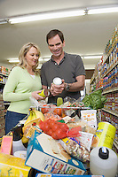 Mature couple look at jar in supermarket aisle