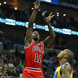 February 12, 2011; New Orleans, LA, USA; Chicago Bulls shooting guard Ronnie Brewer (11) shoots over New Orleans Hornets power forward David West (30) during the first quarter at the New Orleans Arena.   Mandatory Credit: Derick E. Hingle