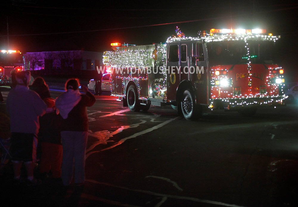 Town of Wallkill, New York  - People watch a fire truck decorated with lights drive by during the Holiday Parade and Tree Lighting in front of Town Hall on Saturday, Nov. 26, 2012.