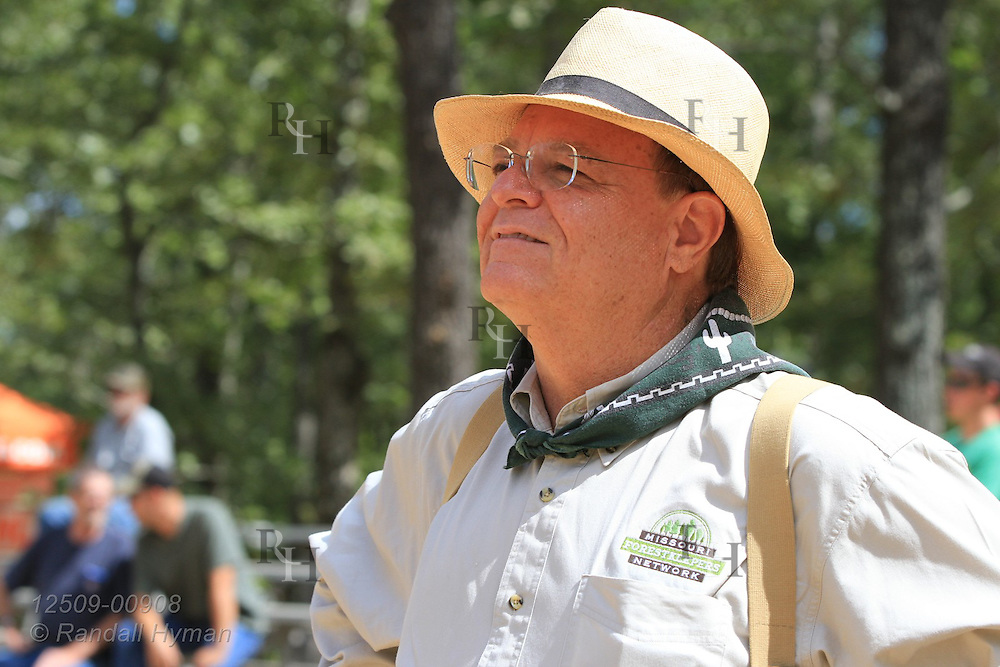 Conservationist watches ultra-mechanized clearcutting of an Ozarks woodland at Missouri In Woods Logging Demo near Viburnum, Missouri.
