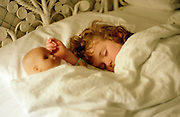 A six year old girl sleeping with her doll beside her