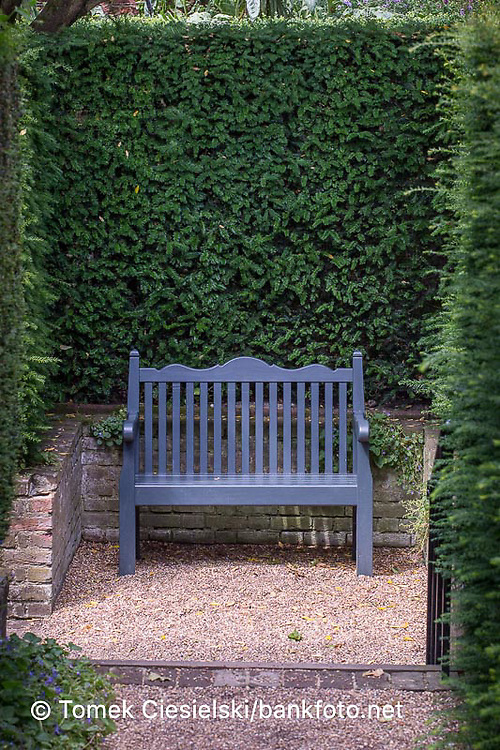 Wooden bench set in  a shady corner
