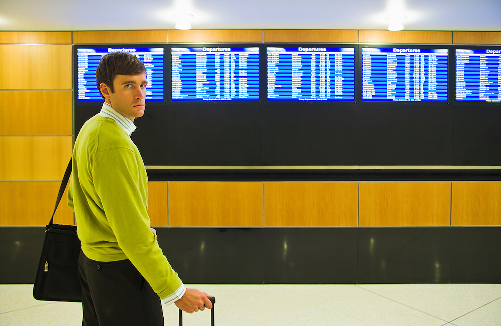 A business man portrait in front of the departures board at an airport.