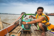 18 JUNE 2013 - YANGON, MYANMAR:    A river taxi boatman drives his boat up the Yangon River. Many working class Burmese live on the far side of the river and the boats to commute to and from work every day.    PHOTO BY JACK KURTZ