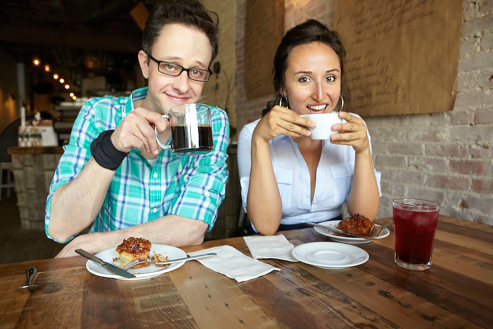 Lifestyle image of young couple drinking coffee and tea inside cafe