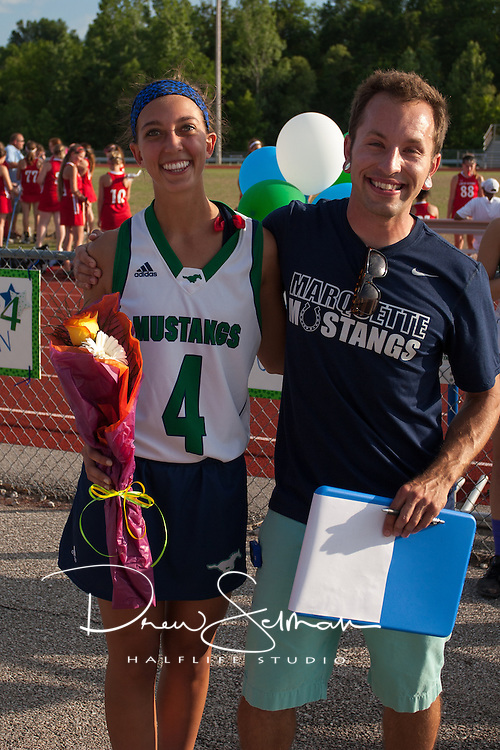 Marquette High School Senior Lacrosse player, Lauren Wellman (4) is honored at halftime against Barat Academy. Coach Chris Elledge, also pictured, read a short bio of each player.  Marquette won the game 15 to 0.