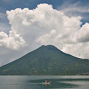 A fisherman passes under the volcano San Pedro, on Lago de Atitlan, Guatemala.  Photo by William Byrne Drumm.
