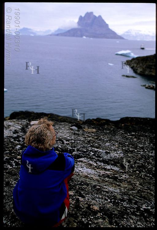 Woman sits on granite ledge overlooking fjord, cruise ship and distant Uummannaq Island; Qilakitsoq, Greenland.
