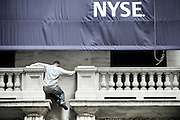 A maintenance worker climbs the facade of the NYSE - New York Stock Exchange on the same day as the House rejected the bail-out package in September 2008