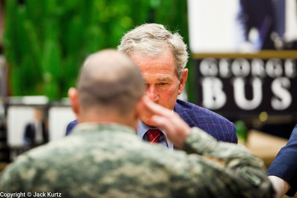 """09 DECEMBER 2010 - PHOENIX, AZ: Former President GEORGE W. BUSH salutes an American soldier and signs copies of his book, """"Decision Points"""" at the Barnes & Noble Bookstore in Phoenix, AZ, Thursday, Dec. 9. More than 2,000 people lined up starting at 5AM to get copies of the former President's book, """"Decision Points."""" A handful of protesters demonstrated against President Bush near the bookstore, calling him a """"war criminal.""""  PHOTO BY JACK KURTZ"""