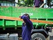 11 JULY 2017 - BANGKOK, THAILAND: Bangkok city workers take trash to a waiting truck while clearing 20 homes from the Khiao Khai Ka community along the Chao Phraya River. The community is the first to be evicted as the city goes ahead with its plan to build a 14 kilometer long (22 mile) riverfront promenade. Thousands of families are expected to be evicted to make way for the promenade. Residents in the Khiao Khai Ka community agreed to leave voluntarily and will receive compensation for their homes. The exact amount of the compensation has not been determined.      PHOTO BY JACK KURTZ