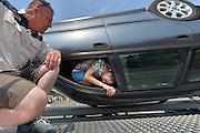 Nederland, Beneden Leeuwen, 5-7-2015Ongevalssimulator. De auto draait ondersteboven en de inzittende moet aan de hand van aanwijzingen van de instructeur uit de autogordel en de auto zelf zien te komen.Foto: Flip Franssen