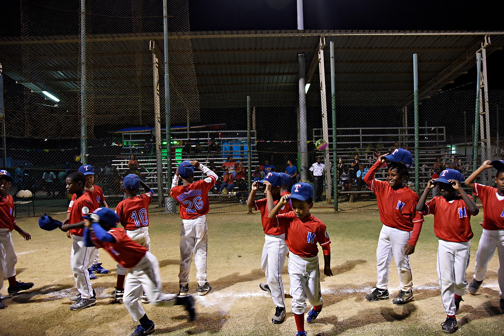 WILLEMSTAD, CURACAO - DECEMBER 10, 2014: Marchena Hardware players tip their hats to the crowd after defeating team Trai Seru 12-3 during a tournament at the Frank Curiel field. The team wears Texas Rangers hats because Rangers player Jurickson Profar's little brother Jurdrick Profar is on the team. (photo by Melissa Lyttle)